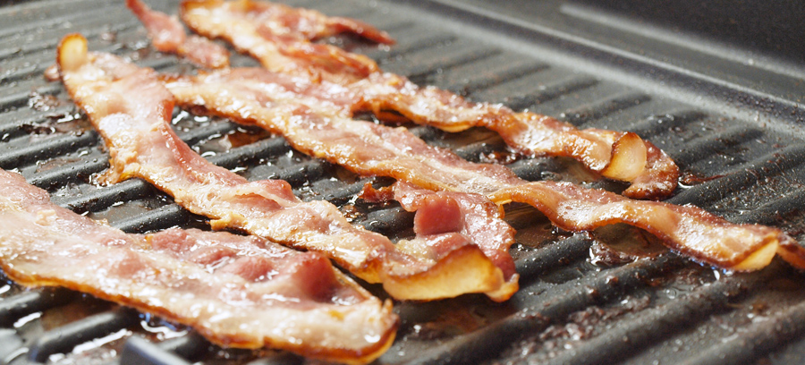 Cooking strips of bacon on the grill