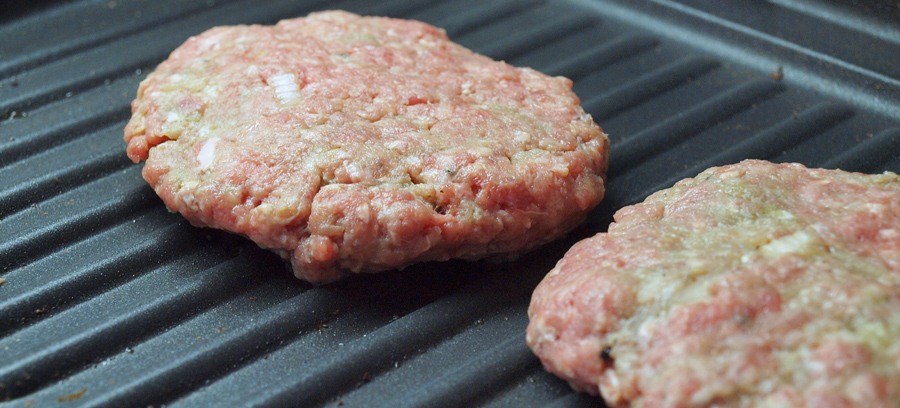 Beef patties cooking on the grill